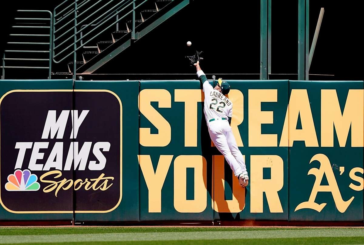 Ramon Laureano #22 of the Oakland Athletics leaps at the wall to take a home run away from Teoscar Hernandez #37 of the Toronto Blue Jays in the top of the second inning of a Major League baseball game at Oakland-Alameda County Coliseum on April 21, 2019 in Oakland, California.