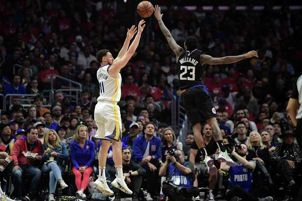 Golden State Warriors guard Klay Thompson, left, shoots as Los Angeles Clippers guard Lou Williams defends during the first half in Game 4 of a first-round NBA basketball playoff series Sunday, April 21, 2019, in Los Angeles.