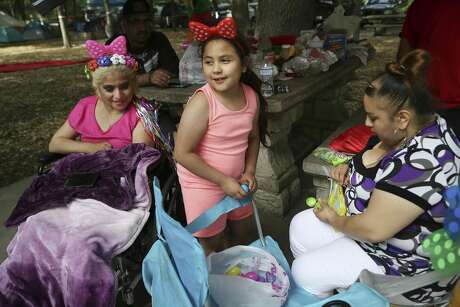Gabriella Lara, 8, center, helps fill Easter eggs with Adriana Gonzalez, right, and Jackie Lara, left, at Brackenridge Park, Sunday, April 21, 2019. Thousands gathered at Brackenridge and other city parks for Easter Sunday fun.