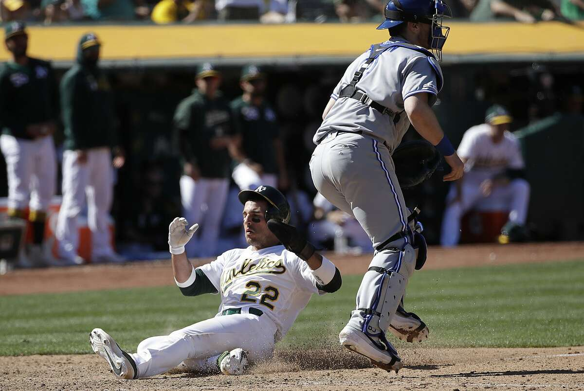Oakland Athletics' Ramon Laureano (22) scores past Toronto Blue Jays catcher Danny Jansen during the eighth inning of a baseball game in Oakland, Calif., Sunday, April 21, 2019.