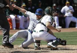 Toronto Blue Jays' Brandon Drury, left, scores past Oakland Athletics catcher Nick Hundley during the sixth inning of a baseball game in Oakland, Calif., Sunday, April 21, 2019. (AP Photo/Jeff Chiu)