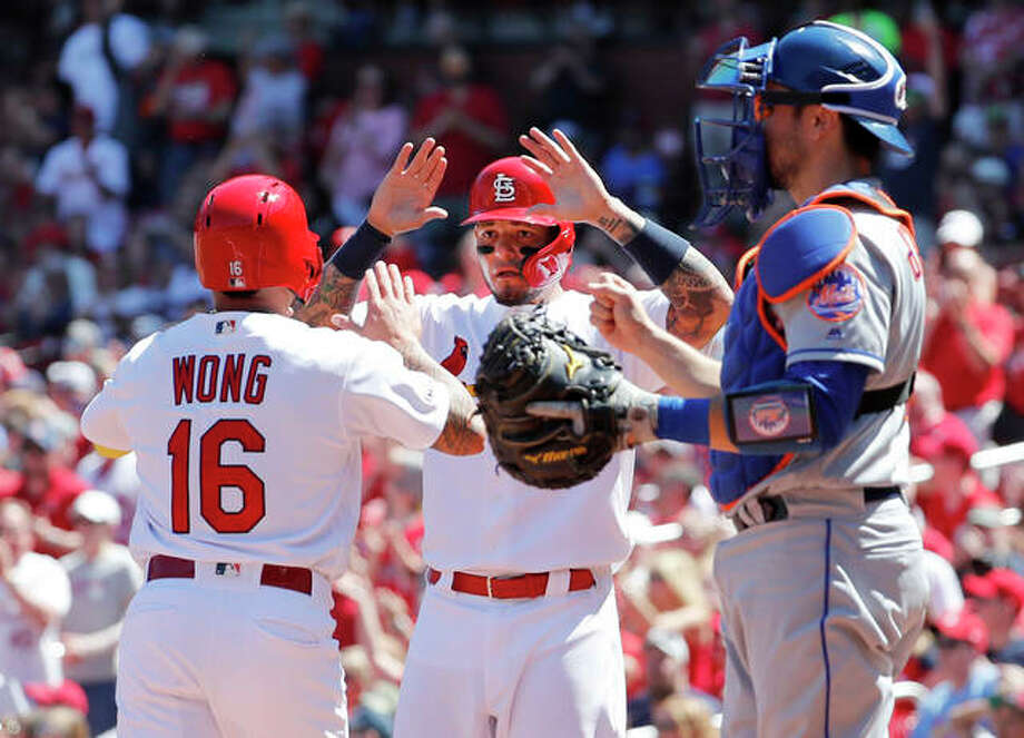 The Cardinals' Kolten Wong (16) and teammate Yadier Molina celebrate after scoring runs while Mets catcher Travis d'Arnaud (right) watches in the second inning Sunday at Busch Stadium. Photo: Associated Press