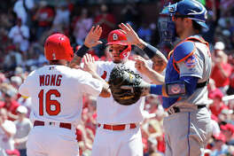 The Cardinals' Kolten Wong (16) and teammate Yadier Molina celebrate after scoring runs while Mets catcher Travis d'Arnaud (right) watches in the second inning Sunday at Busch Stadium.