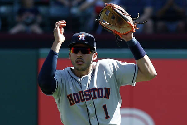 Houston Astros shortstop Carlos Correa (1) loses the ball in the sun on a pop fly by Texas Rangers' Joey Gallo during the sixth inning of a baseball game Sunday, April 21, 2019, in Arlington, Texas. (AP Photo/Mike Stone)