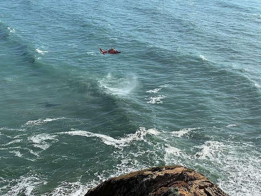 A rescue crew in a helicopter works off the coast of Pacifica on Sunday, April 21, 2019, after a hang glider went down in the water in a fatal incident.