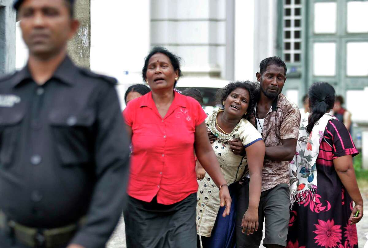 Relatives of a blast victim grieve outside a morgue in Colombo, Sri Lanka, Sunday, April 21, 2019. More than hundred were killed and hundreds more hospitalized with injuries from eight blasts that rocked churches and hotels in and just outside of Sri Lanka's capital on Easter Sunday, officials said, the worst violence to hit the South Asian country since its civil war ended a decade ago. (AP Photo/Eranga Jayawardena)