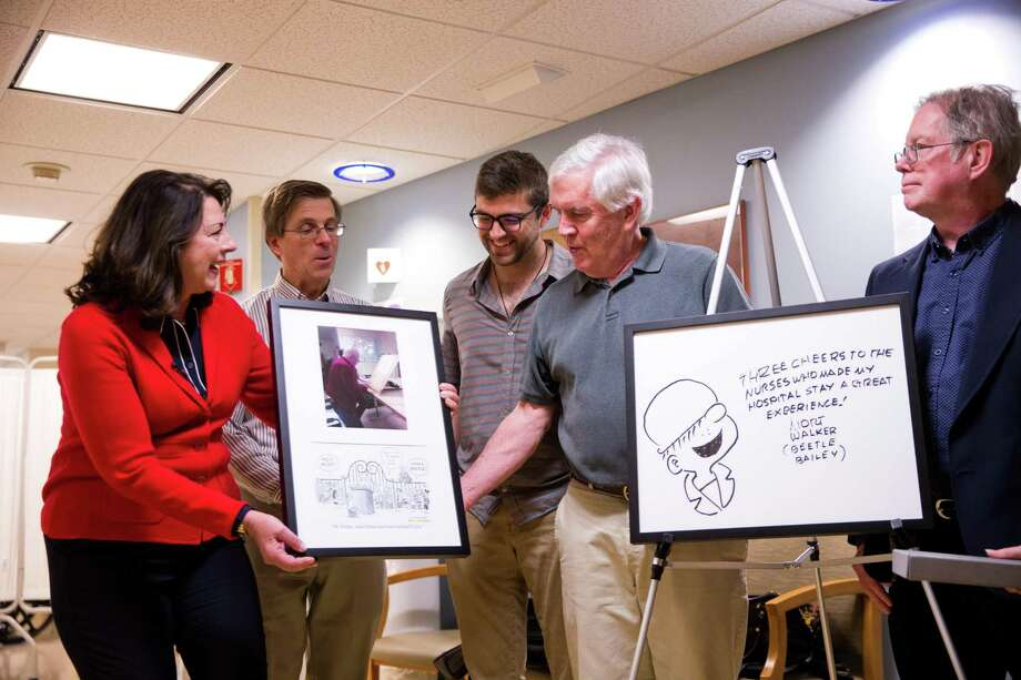 """Brian Walker, son of the late Mort Walker, receives a framed image of one of his father's final days at Stamford Hospital before his death, accompanied by a comic strip by Bill Janocha in tribute to Mort Walker's life. Mort Walker was the creator and illustrator of the """"Beetle Bailey"""" comic strip, that began in the 1950s and is still in production. Stamford Health President and CEO Kathleen Silard is handing over the framed picture. An image of Mort Walker's final Beetle Bailey drawing will hang outside of the hospital's rehabilitation center. Also pictured, from left to right, are Janocha, Brian Walker's son David, and Mort Walker's son Greg Walker. Photo: Contributed Photo / Minush Krasniqi / Stamford Advocate Contributed"""