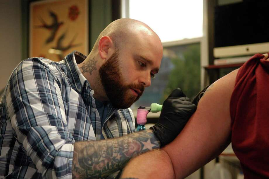 Eric Tymula, a co-owner of Danbury Tattoo and Piercing, touching up a tattoo on Friday, April 19, 2019. Photo: Rob Ryser / Hearst Connecticut Media