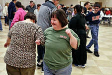 """Brooke Wells (left) and Melissa Waller dance during """"The Hokey Pokey"""" at the Decatur Park District's Special Recreation Association dances at the Knights of Columbus Hall in Decatur. For more than 25 years, individuals with special needs have attended the event to dance to their favorite music."""