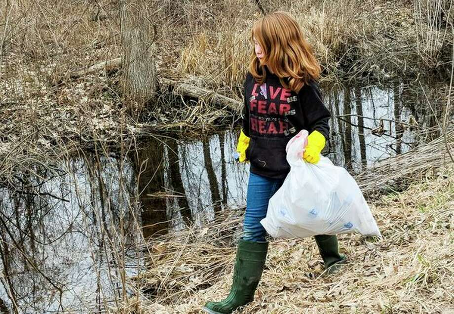 Mackenzie Knake of Beaverton, 10, thought the roadside looked disgusting and decided rather than complain, she would help make it better. (Tereasa Nims/for the Midland Daily News)