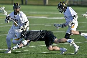 Madison, Connecticut - Wednesday, April 17, 2019: Sam Norris of Xavier H.S., center, takes a tumble against Jack Flanagan of Daniel Hand H.S. during first quarter of boys lacrosse Wednesday at Strong Field in Madison. Xavier H.S. defeated Daniel Hand H.S. 10-5.