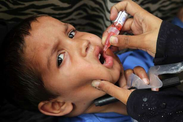 A health worker gives a polio vaccination to a child in Lahore, Pakistan, Monday, April 22, 2019. A Pakistani health official says the country has kicked off a nationwide polio vaccination campaign for the year in efforts to eradicate the crippling disease by the end of 2019. Pakistan reported only eight new polio cases in 2018.