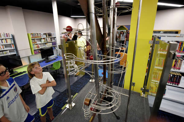 Youngsters explore the children's section following a dedication ceremony April 4 at the newly renovated Midland County Public Library downtown branch.