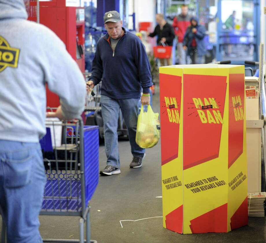 Customers of Shop Rite pass by a recycling bin and a large sign after shopping on Saturday, April 20, 2019 in Stamford. The owner of the store, Dominick Cingari, recently put up the large yellow signs to serve as a reminder that a plastic bag ban goes into effect May 3. Photo: Matthew Brown / Hearst Connecticut Media / Stamford Advocate