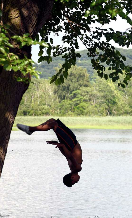 A teen practices flips in New Haven next to the Quinnipiac River with a group of friends. Photo: Arnold Gold / Hearst Connecticut Media
