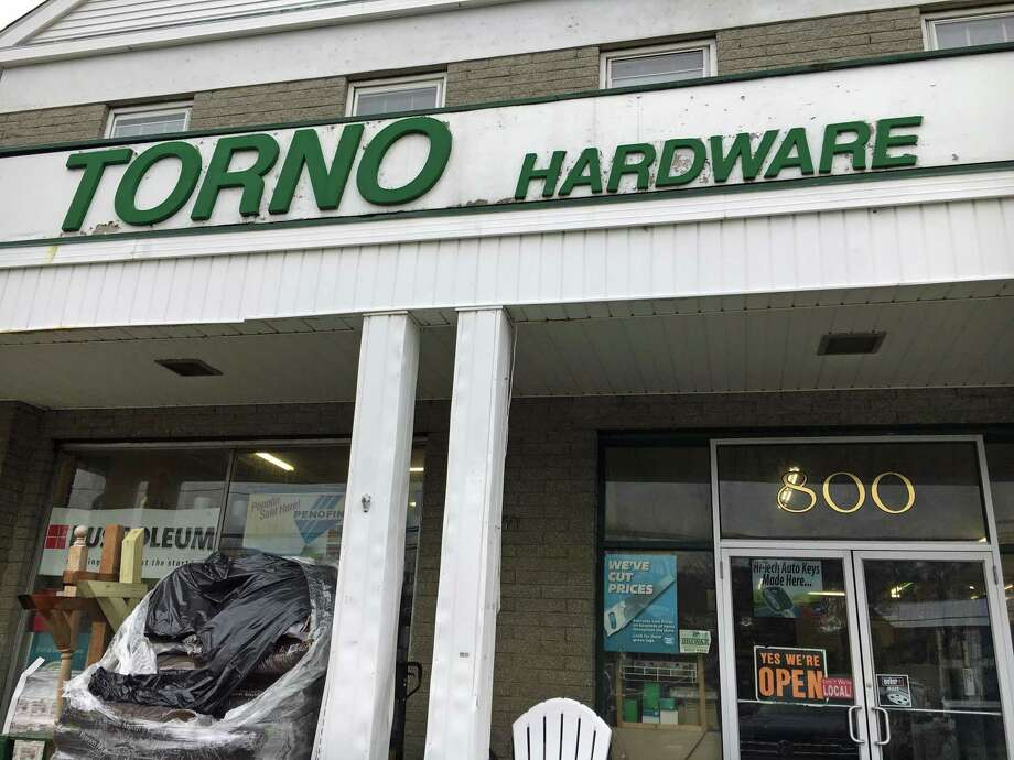 Torno Hardware storefront on Post Road East in Westport, with a sign reminding shoppers that they're open, at least for now. Photo: Melanie Espinal / For Hearst Connecticut Media