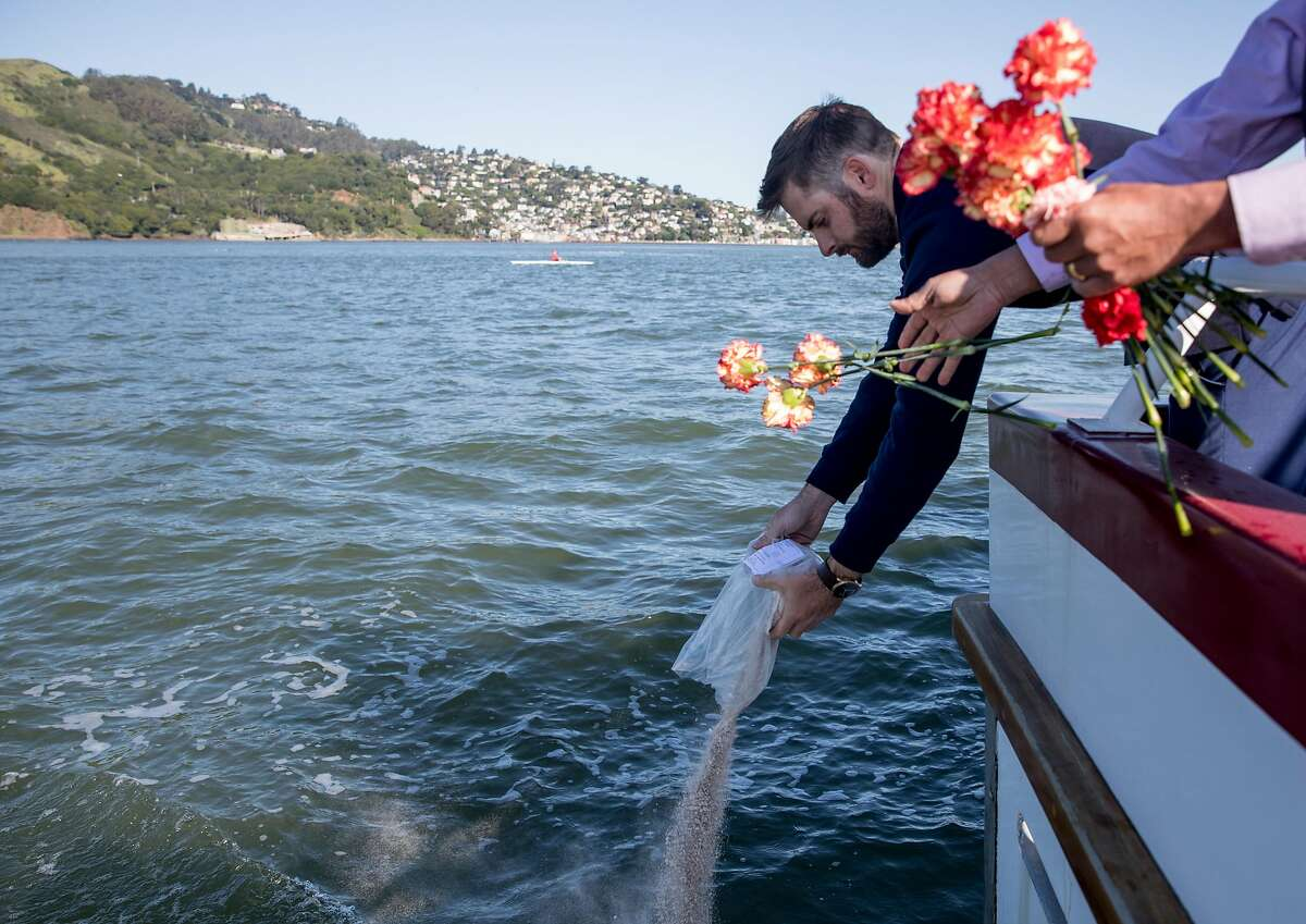 Deck Hand Jake Adams scatters cremated ashes as Clergy Titus George tosses carnations into the bay during a ceremony on the Neptune Society of Northern California's boat on the San Francisco Bay in San Francisco, Calif. Wednesday, April 10, 2019.