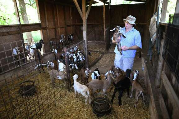 Robert Ragels holds a kid on his family's goat farm in New Braunfels.