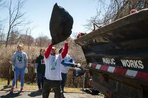 Kumar Patel tosses a bag of garbage after helping clean up Andrews Field with the Shop Rite Green Team during the Mayor's Citywide Earth Day Spring Cleanup in Norwalk, Conn. on Saturday, April 21, 2018.