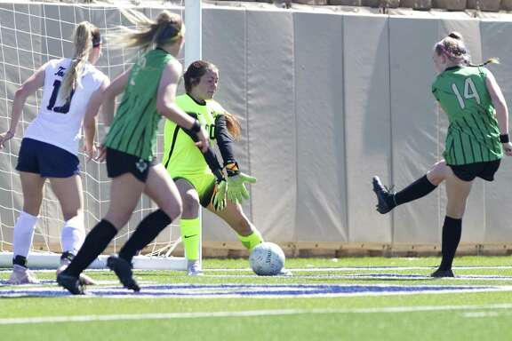 Southlake Carroll forward Madison Drenowatz (14) gets a shot past Katy Tompkins goalie Rebekah Jordan (00) in the first period of the Class 6A girls state championship match during the UIL State Soccer Championships at Birkelbach Field on Saturday, April 20, in Georgetown.