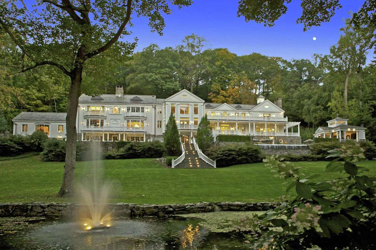 The rear view of the 12,536-square-foot house shows its grand staircase, multiple stone terraces, pool house, and pond with fountains and lighting.