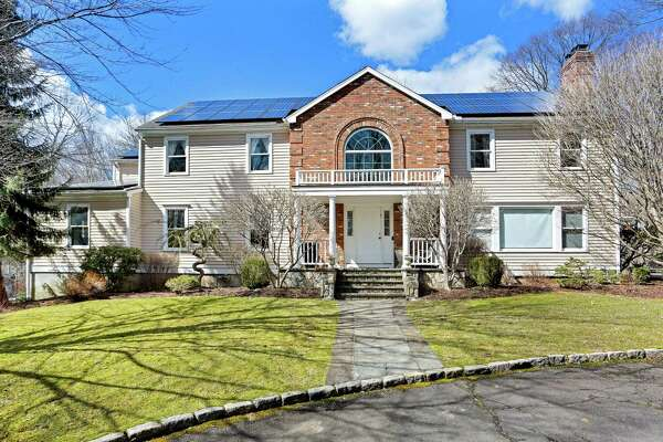 The roof of the beige clapboard and red brick colonial house at 190 Governors Lane in Lower Greenfield Hill is covered in solar panels reducing energy consumption and fuel bills.