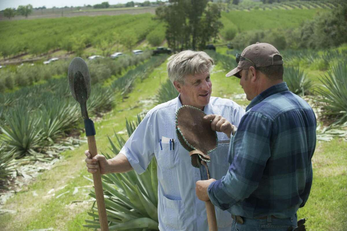 Craig Reynolds and Raul Chavez hold coas, the tool used to harvest the piña from the agave plant.