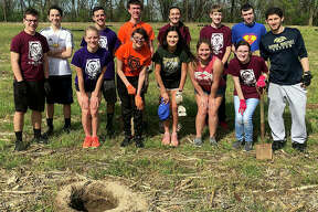 Father McGivney Catholic High School students pause during their planting work Monday at Drda Woods in Edwardsville to celebrate Earth Day. The students are: Aaron Boulanger; Patrick Boulanger; Olivia Fults; Jeremy Harkins; Joanna Hunter, Marta Korte, Christopher Landoll, Michael Landoll, Claire McKee, Chalet Micun, Lauren Meyer, Luke Taylor and teacher Tim Vance.
