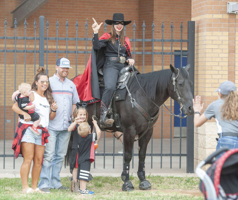 Texas Tech University fans and supporters take a picture with the Masked Rider April 5 before the annual football scrimmage at Grande Communications Stadium. The mascot was unmasked on Friday during a ceremony at the Lubbock campus. Lyndi Starr served as Masked Rider for 2018-19, and has handed over the reins to Emily Brodbeck. Photo: Tim Fischer/Reporter-Telegram