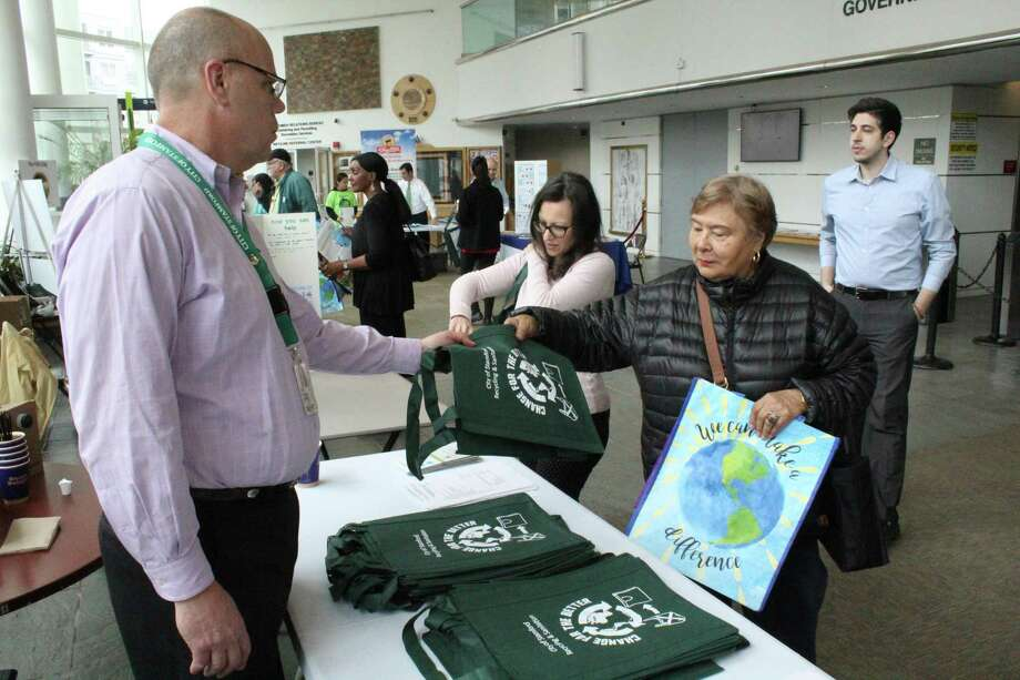 Dan Colleluori, supervisor of recycling and sanitation for Stamford, hands out a tote bag to Stamford resident Oliva Grube during an Earth Day event on Monday, April 22, 2019. The design on the green bag was created by Dolan Middle School eighth grader Kaitlin Doyle as part of a citywide competition. Photo: Ignacio Laguarda / Hearst Connecticut Media / Stamford Advocate