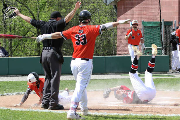 Edwardsville batter Drake Westcott (33) make the call after the Tigers' Hayden Moore dives safely across home plate on a passed ball as Alton pitcher Adam Stilts is too late with the tag in the first inning Monday at Alton High in Godfrey.