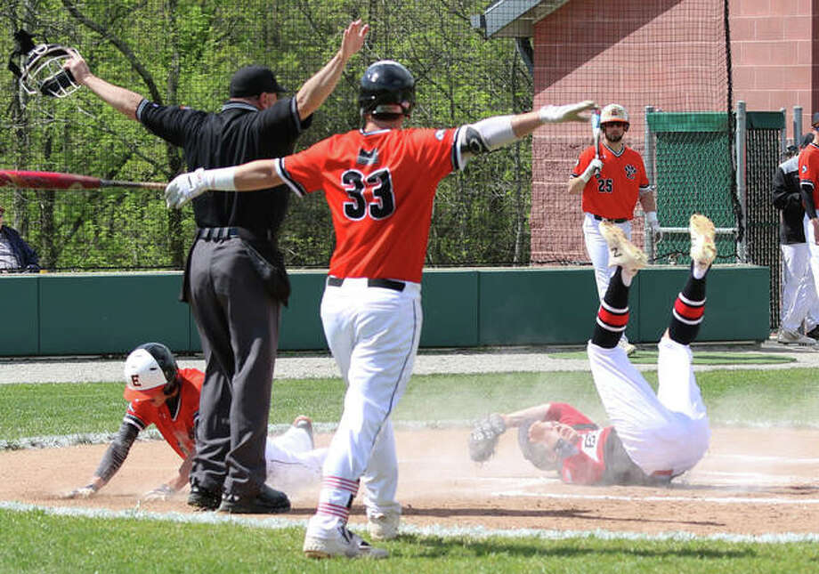 Edwardsville batter Drake Westcott (33) make the call after the Tigers' Hayden Moore dives safely across home plate on a passed ball as Alton pitcher Adam Stilts is too late with the tag in the first inning Monday at Alton High in Godfrey. Photo: Greg Shashack / The Telegraph