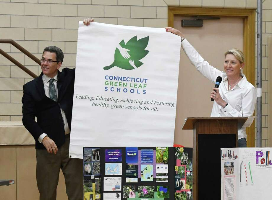 Principal Christopher Weiss and teacher Audrey Barrett celebrate Riverside School's new recognition as a CT Green Leaf School by the COEEA during the Earth Day kickoff event at Riverside School in the Riverside section of Greenwich, Conn. Monday, April 22, 2019. At the event, Principal Christopher Weiss shared stories of his spring vacation to several National Parks, the Riverside Chorus performed a Navajo poem, students shared their STEM Fair projects on plant life and air pollution, and the . Photo: Tyler Sizemore / Hearst Connecticut Media / Greenwich Time