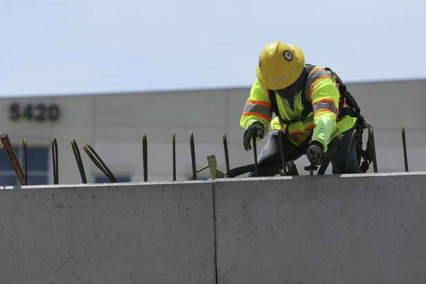 Construction workers tie steel for a barrier on the new ramp south of the Loop 610 interchange with Interstate 69 on April 22.