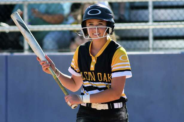 Klein Oak 2nd baseman Allie Saville is all smiles as she looks to Coach Barry Wilson for a sign during her at-bat in the top of the third inning against Klein in their District 15-6A play-in game at Klein Cain High School on April 19, 2019.