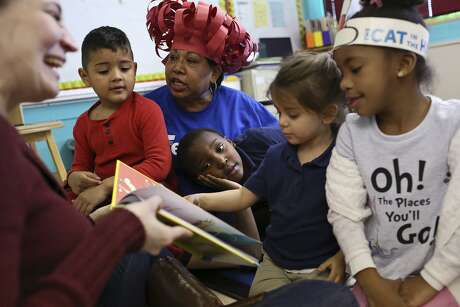 "A volunteer with the United Way reads ""One Fish Two Fish Red Fish Blue Fish"" to students and their after-school teacher at Tynan Early Childhood Education Center in San Antonio in 2017. New funding priorities at United Way seek to help all area children reach their full potential."