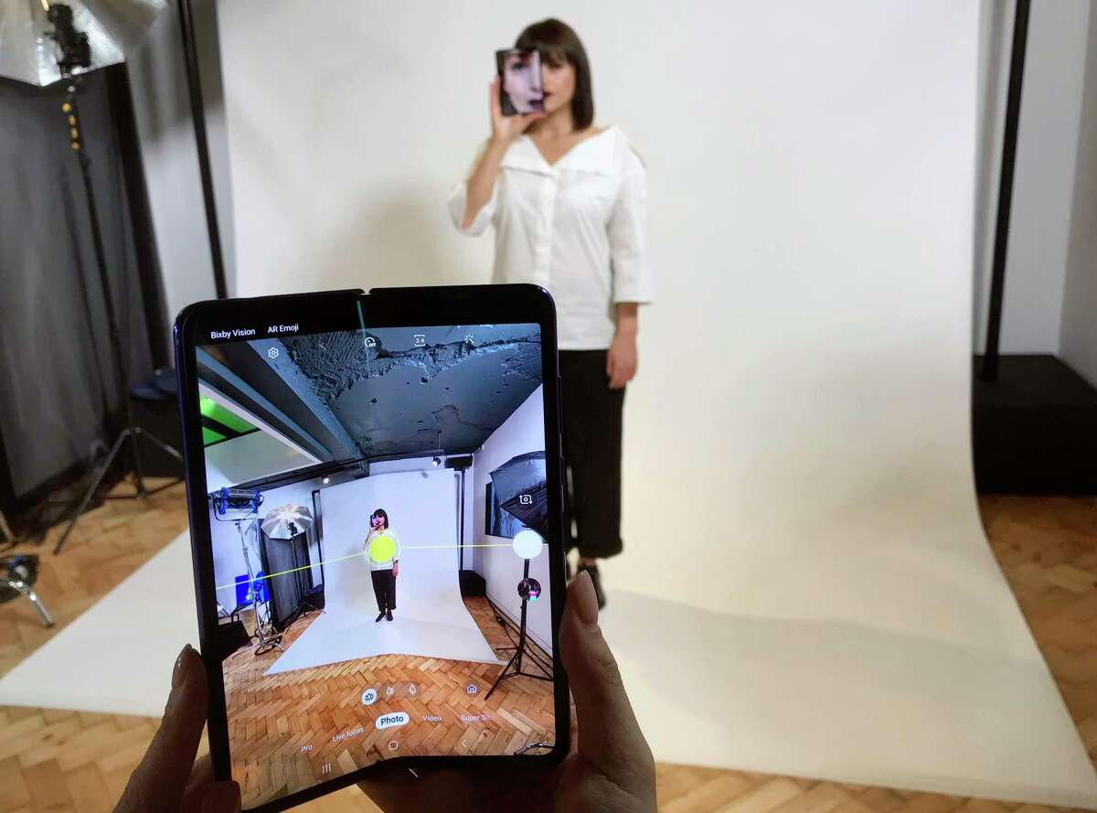 FILE - In this April 16, 2019, file photo, a model holds a Samsung Galaxy Fold smart phone to her face, during a media preview event in London. Samsung is pushing back this week's planned public launch of its highly anticipated folding phone after reports that reviewers' phones were breaking. The company had been planning to release the Galaxy Fold on Friday. Instead, it says it will to run more tests and announce a new launch date in the coming weeks. (AP Photo/Kelvin Chan, File)