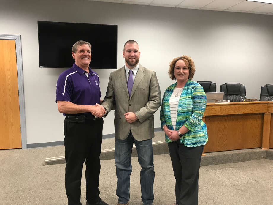 Drew Johnston stands with Superintendent Michelle Barrow and School Board President Donnie Meek after being approved to be the new head football coach and athlete director of Newton Independent School District. Photo: Meshach Sullivan  / The Enterprise