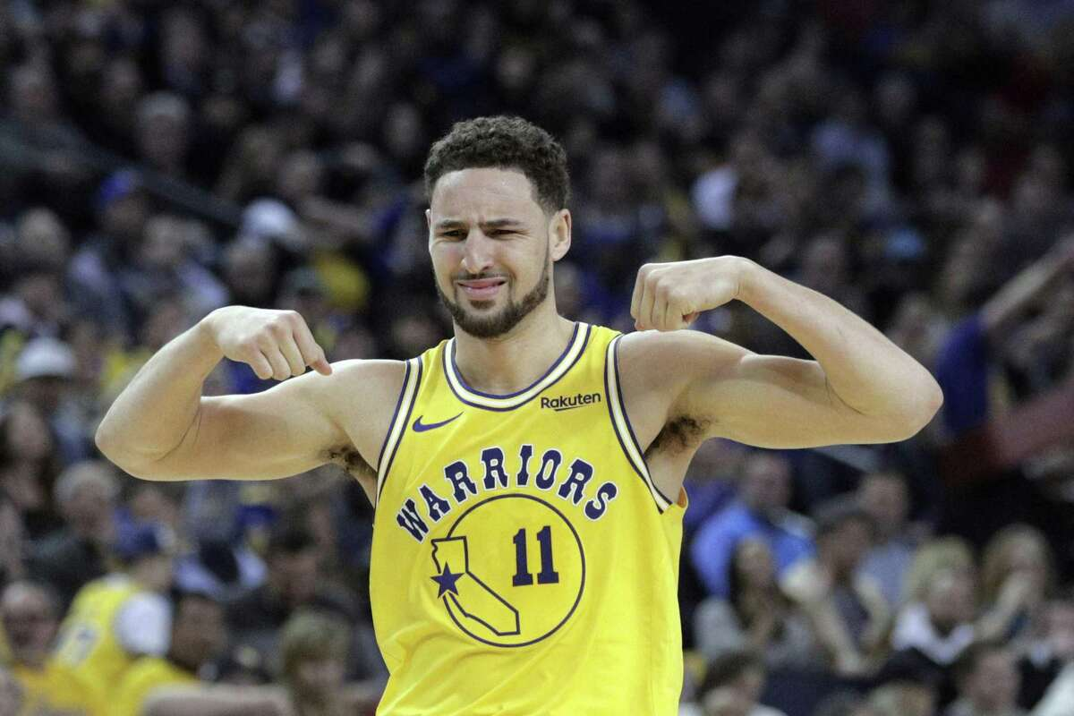 Klay Thompson (11) gestures to Kevon Looney (5) after Looney made a shot and was fouled in the first half as the Golden State Warriors played the Houston Rockets at Oracle Arena in Oakland, Calif., on Thursday, January 3, 2019.
