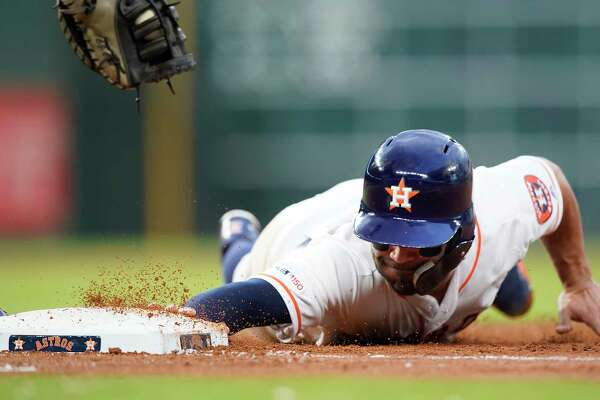 Houston Astros second baseman Jose Altuve (27) slides back safely to first in the first inning against Minnesota Twins at Minute Maid Park on Monday, April 22, 2019.
