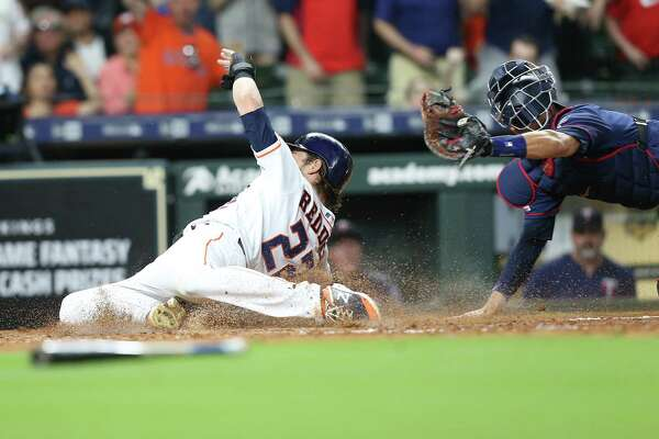 Houston Astros right fielder Josh Reddick (22) is tagged out as he slides into home under Minnesota Twins catcher Jason Castro (15) at Minute Made Park on Monday, April 22, 2019.