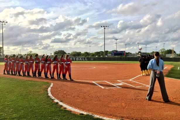 The West Brook Bruins softball team stands along the third base line prior to its tiebreaker matchup against Channelview at Baytown Sterling High School.