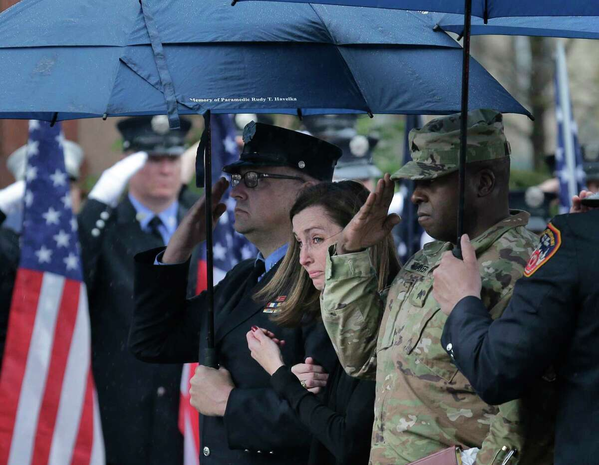 Shannon Slutman, wife of Staff Sgt. Christopher Slutman, reacts as a casket containing her husband's body is moved into a funeral home in the Bronx borough of New York, Monday, April 22, 2019. Firefighters in three states are honoring the U.S. Marine and New York City firefighter who was killed by a roadside bomb in Afghanistan. (AP Photo/Seth Wenig)