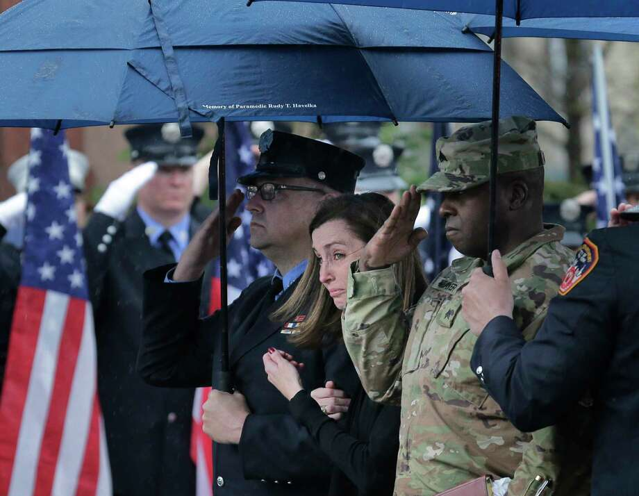 Shannon Slutman, wife of Staff Sgt. Christopher Slutman, reacts as a casket containing her husband's body is moved into a funeral home in the Bronx borough of New York, Monday, April 22, 2019. Firefighters in three states are honoring the U.S. Marine and New York City firefighter who was killed by a roadside bomb in Afghanistan. (AP Photo/Seth Wenig) Photo: Seth Wenig / Copyright 2019 The Associated Press. All rights reserved.