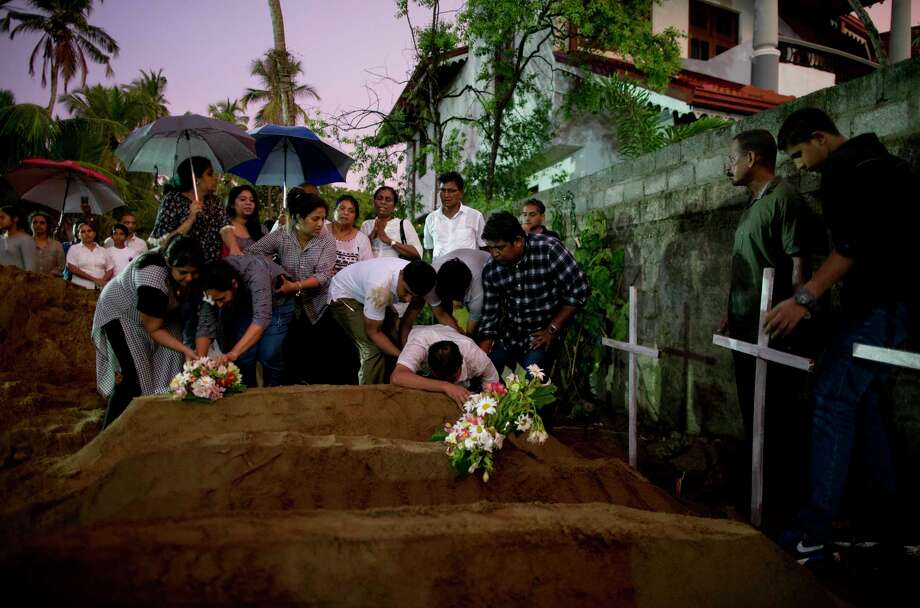 Relatives place flowers after the burial of three victims of the same family, who died at Easter Sunday bomb blast at St. Sebastian Church in Negombo, Sri Lanka, Monday, April 22, 2019. Easter Sunday bombings of churches, luxury hotels and other sites was Sri Lanka's deadliest violence since a devastating civil war in the South Asian island nation ended a decade ago. (AP Photo/Gemunu Amarasinghe) Photo: Gemunu Amarasinghe / Copyright 2019 The Associated Press. All rights reserved.