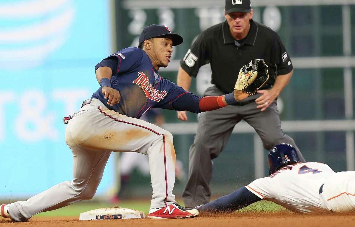 Houston Astros center fielder George Springer (4) slides in under Minnesota Twins second baseman Jonathan Schoop (16) at Minute Made Park on Monday, April 22, 2019.