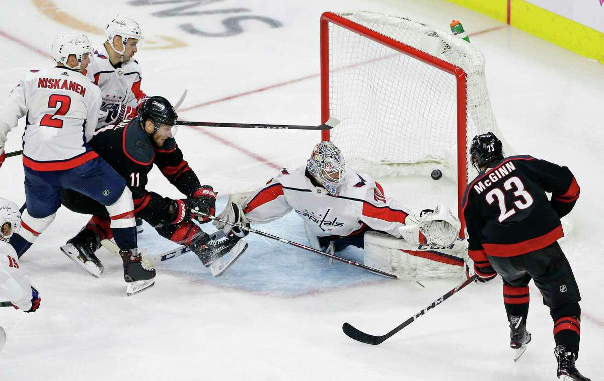 Carolina Hurricanes' Jordan Staal (11) scores the winning goal against Washington Capitals goalie Braden Holtby (70) while Hurricanes' Brock McGinn (23) assists during the third period of Game 6 of an NHL hockey first-round playoff series in Raleigh, N.C., Monday, April 22, 2019. Capitals' Matt Niskanen (2) and Dmitry Orlov, left, of Russia, defend. (AP Photo/Gerry Broome)