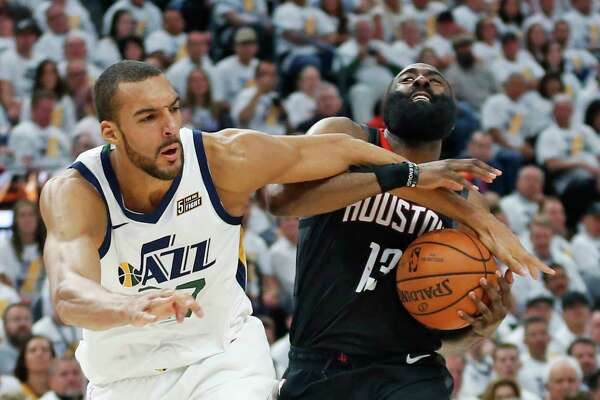 Utah Jazz center Rudy Gobert, left, fouls Houston Rockets guard James Harden (13) as he drives to the basket in the first half during Game 4 of a first-round NBA basketball playoff series, Monday, April 22, 2019, in Salt Lake City. (AP Photo/Rick Bowmer)