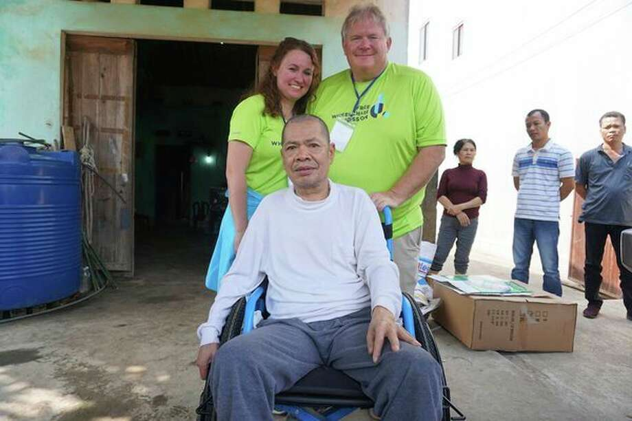 Right at Home Northern Michigan owner Jim Gall, standing right, and his wife Melinda Gall pose for a photograph with Dao, a man to whom they gifted a wheelchair during a trip to Vietnam representing Right at Home and Free Wheelchair Mission, in November 2018. (Photo provided / Jim Gall)