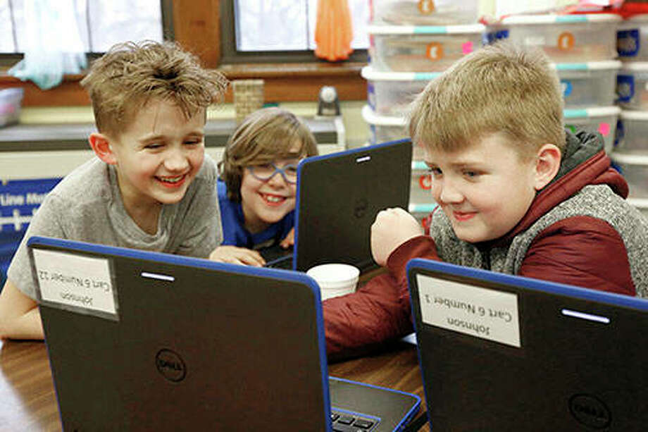 "Third-graders Philip Petrini, Charles ""Obi"" O'Brien and Coltyn Schutte laugh while producing a PowerPoint presentation on statistics during Baldwin's Flight Academy in Quincy. The club gives third- through fifth-graders an opportunity to explore science, technology, engineering and math through activities and group projects after school. Photo: Katelyn Metzger 